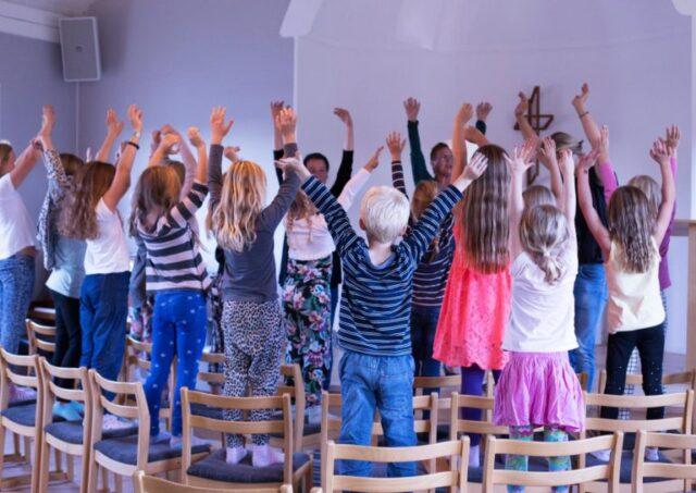 Barn står på stolar med uppsträckta armar