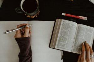 Bibel, händer och pennor.