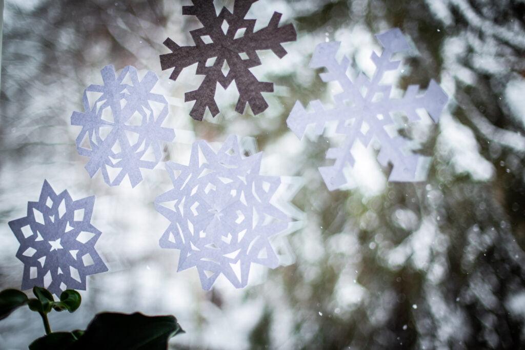 Snöstjärnor av papper på ett fönster